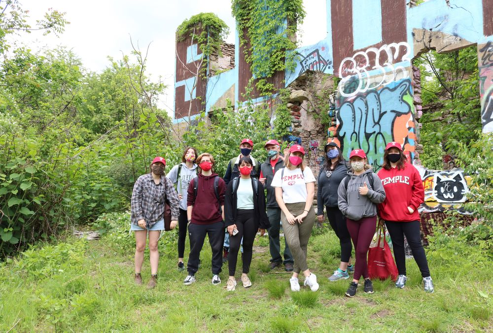 group of Temple students poses in front of graffitied mansion on Sedgley woods disc golf course